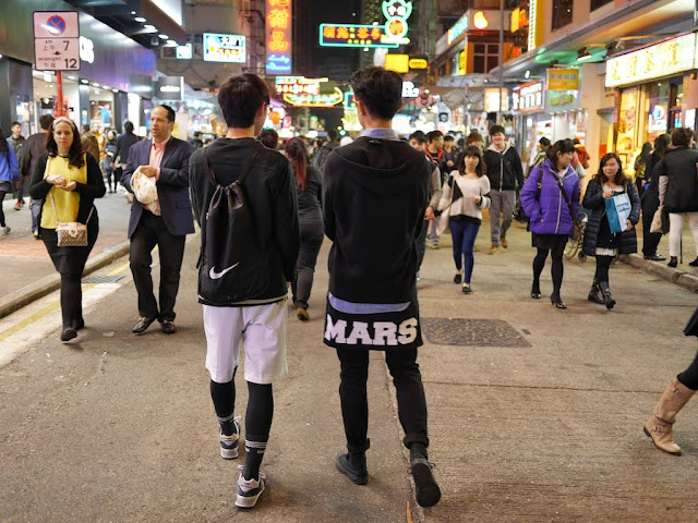 "one young man with a Nike back pouch and another wearing a shit with ""MARS"" on it at Sai Yeung Choi Street South"