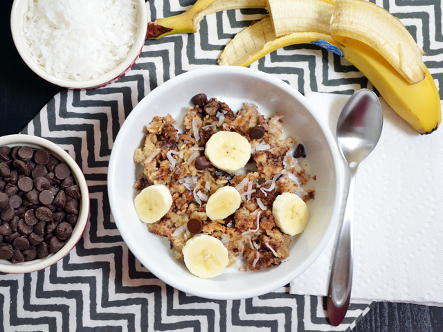 Top view of a bowl of Funky Monkey Baked Oatmeal with a spoon, half a banana, and a cup of chocolate chips on the side