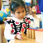Montessori preschool girl in Irvine working with sound cylinders for sensorial development.