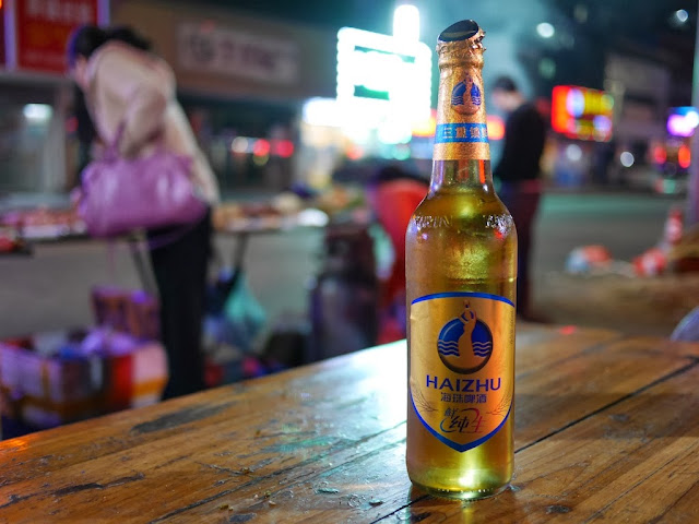 an opened bottle of Haizhu beer sitting on an outdoor table in Zhuhai