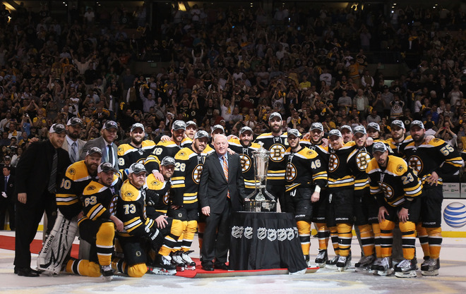 The Boston Bruins gather around the Prince of Wales trophy for pictures