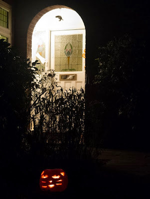 Jack-o-lantern by a doorway at night