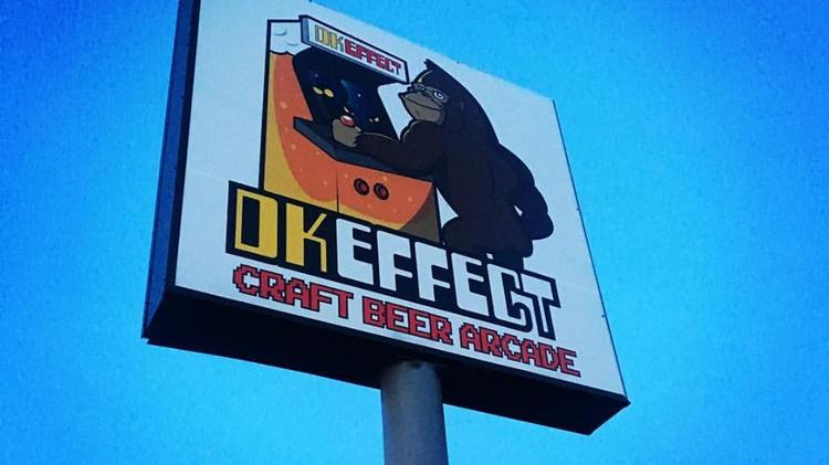 large DK Effect sign with a cartoon of a gorilla playing an arcade game