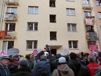 Demonstranten vor Wohnhaus, an dem mehrere Transparente hängen.