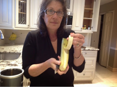 woman holding a peeled plantain in her kitchen