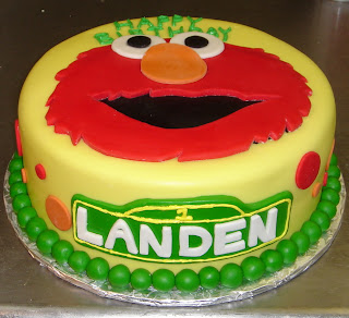 Sesame Street Elmo custom yellow fondant kid's birthday cake with red and orange polka dots and green pearl boarder