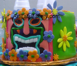 Tiki custom designed luau theme green fondant birthday cake with bright orange, purple and yellow flowers