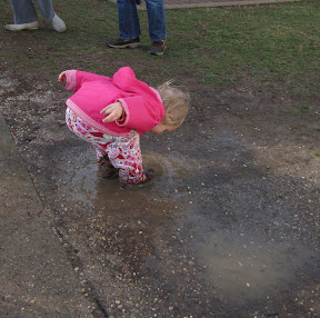 Young child stomping in a rain puddle.