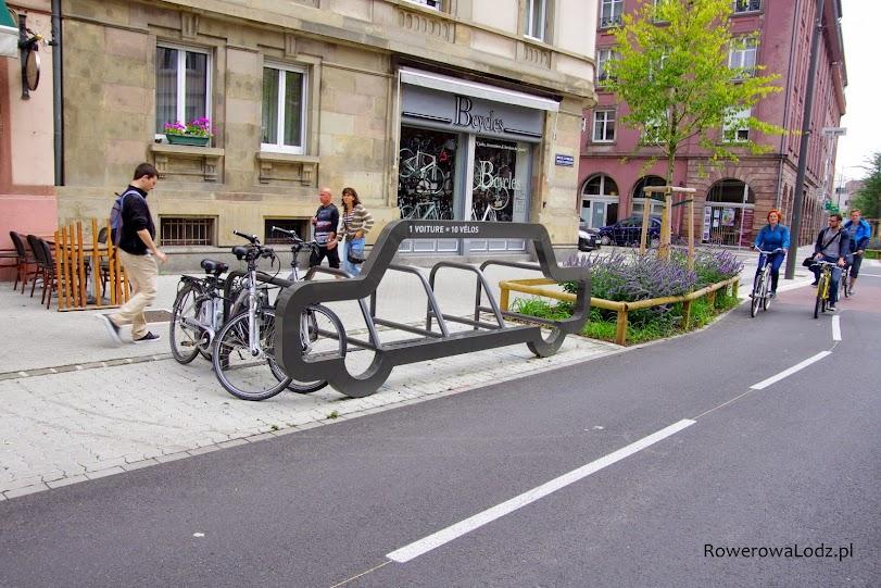 """Na konstrukcji widnieje napis: """"1 auto to aż 10 miejsc dla rowerów"""". W tle sklep rowerowy"""
