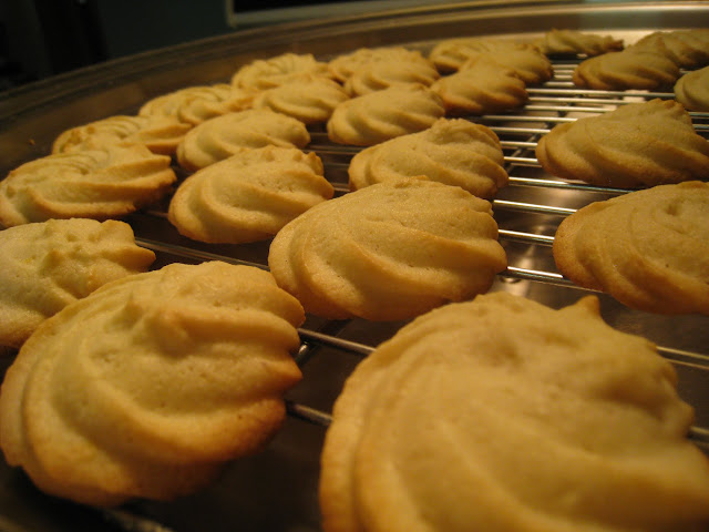 perfectly golden brown piped cookies cooling