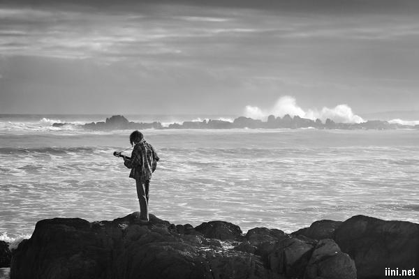 ảnh chàng trai đàn guitar 1 mình trước biển