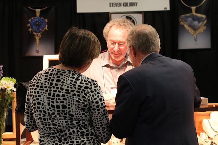 jeweler showing a piece to a couple
