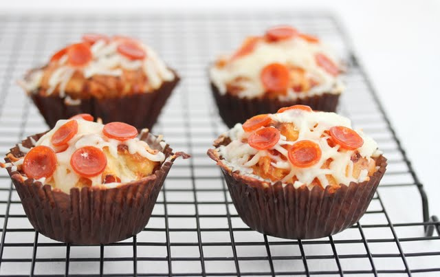 four pizza cupcakes on a baking rack