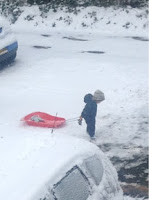 red sled in the snow with toddler pulling it along