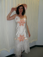 Woman modeling a white dress with pink flowers.