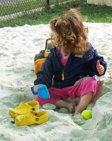 Young child digs into the sand with feet and shovel.