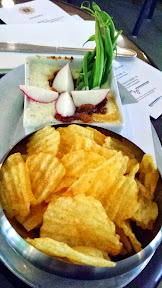 From Barlow Artisanal Bar's Happy Hour menu, the Caramelized Onion Dip is $6 and comes with potato chips and crudite