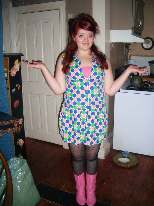 A fat, pale, red-headed woman throws up her hands and shrugs her shoulders. She is wearing a short dress with blue, salmon, and green polka dots and a front zipper. It is zipped low enough to display a pink strapless sports bra. On her legs are black sheer polka dotted stockings and hot pink engineer boots.