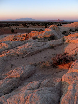 Sunrise glowing on the rocks, with the Henrys and Wild Horse Butte in the background