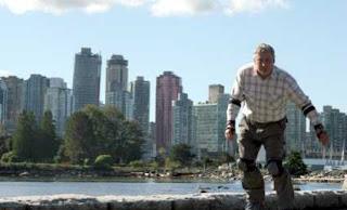 Wolfgang Fabisch auf Inlinern im Stanley Park vor der Skyline Vancouvers