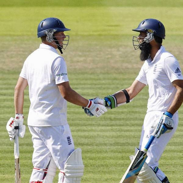 England's Gary Ballance (L) is congratulated by teammate Moeen Ali after reaching a half century (50 runs) during the second day of the second Test cricket match between England and India, at Lord's Cricket Ground in London, England on July 18, 2014.