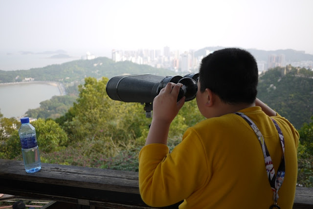 Boy looking through binoculars at Jingshan Park in Zhuhai