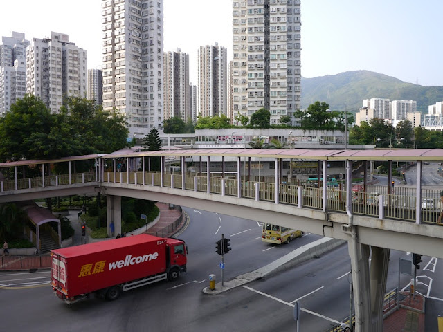 A Wellcome delivery truck passing under an elevated walkway in Tsuen Wan, Hong Kong