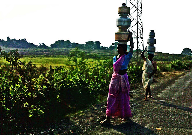 women carrying pots of water on head
