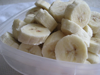 Frozen sliced bananas in a plastic container.