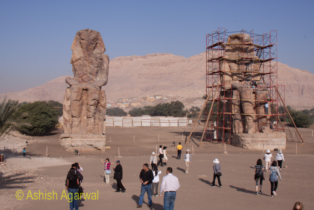 Tourists standing in front of the twin statues of the Colossi of Memnon, outside Luxor, Egypt