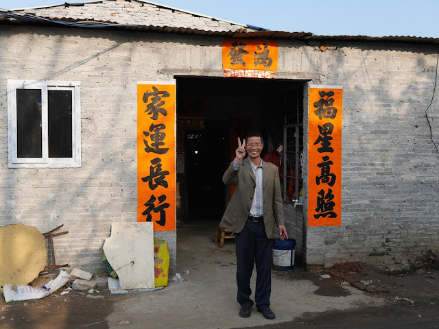 man standing in front of an open entrance to a one-floored building