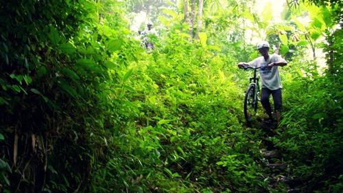 Track turunan disini ganas. Ada undak-undak yang dibuat oleh warga untuk memudahkan pergerakan mereka dalam mendaki bukit. Alhasil, kami harus menuntun sepeda sampai bawah.