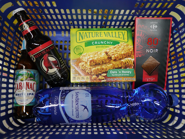 Red Seal Ale, Saranac White IPA, Nature Valley granola bars, 80% dark chocolate, and a bottle of carbonated San Benedetto water in a basket