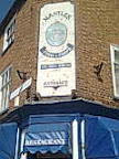 Mantles Fish restaurant pastel & blue signage high up on angled corner brickwork showing olde portrait of building between scrolls