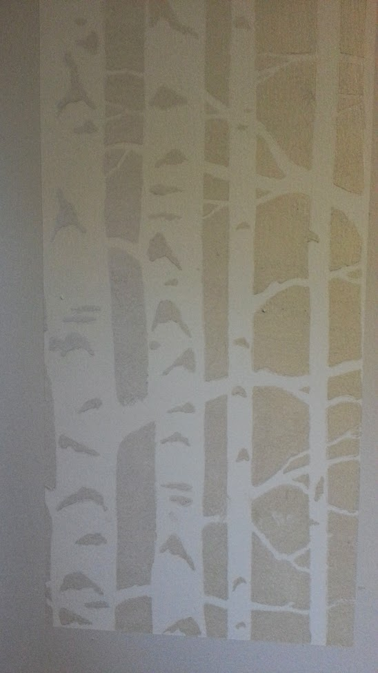 A stenciled design on a white wall showing stylized birch tree trunks