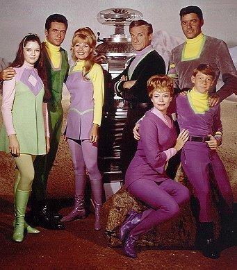 Penny, Major West, Judy, o robô, Dr. Smith e John Robinson, com Maureen e Will Robinson sentados