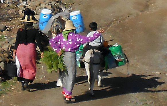 Marokkanische Frauen mit Strohhüten und Kind auf Esel