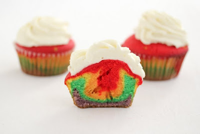 photo of a rainbow cupcake sliced in half with two whole ones behind it