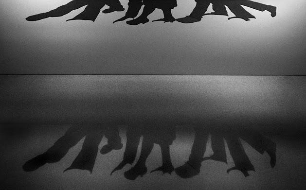 Projecção na parede, das sombras de figuras recortadas, apenas com os pés e pernas