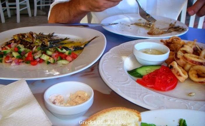 na stole w tawernie plażowej znajdują się talerz greckich dań smażone kałamarnice,ryby, chleb sałatka z pomidorem