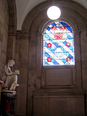 Stained glassed window and statue of woman reading