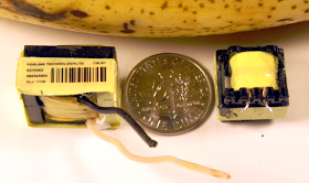 The flyback transformers from an iPad charger (left) and a counterfeit charger (right). Dime and banana are for scale.