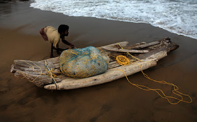 This canoe built with driftwood helps this polio affected youth to go to sea everday for fishing and earn his living. The photograph was shot in Ennore beach in Chennai. India, 2010