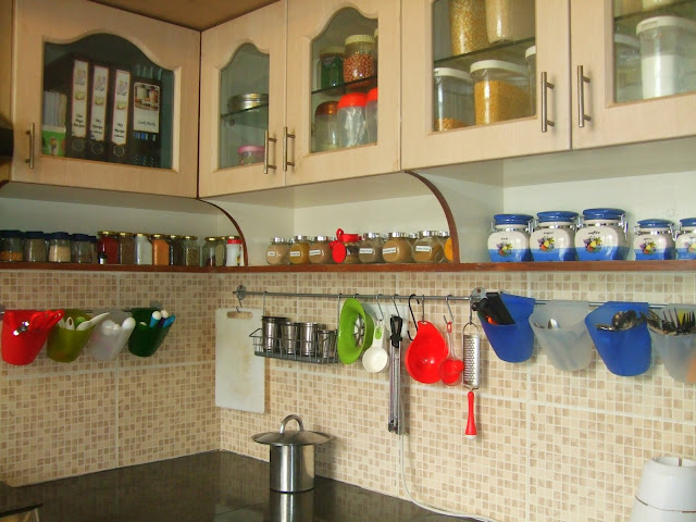 This apartment design boasts of open shelving throughout the house including the kitchen. A traditional Indian kitchen.