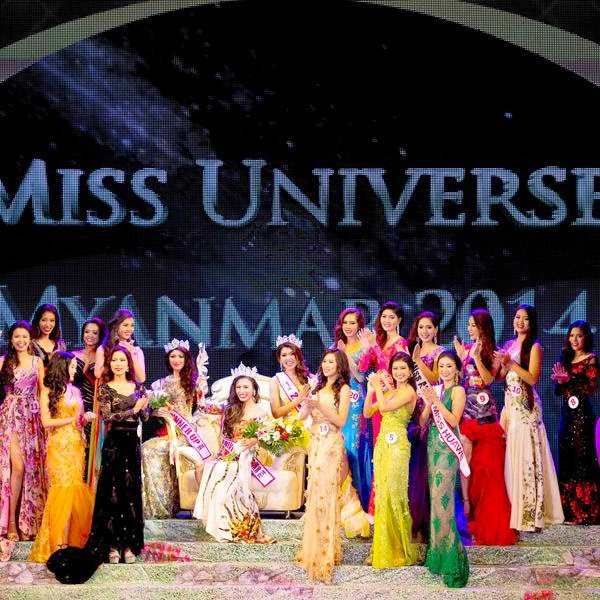 Winner of Miss Universe Myanmar 2014 Sharr Htut Eaindra, center, sits in a chair as she pose for a picture with twenty-finalists during a pageant in Yangon, Myanmar, Saturday, July 26, 2014.