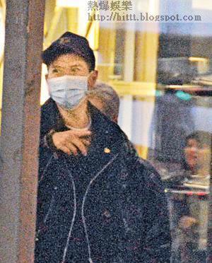 戴口罩的張家輝在中環街頭等過馬路時手指指。