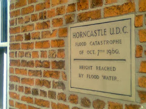 commemoration stone set at around head height, showing the level of the 1960 flood