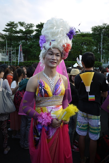 man dressed up in colorful women's clothing and wearing a large wig