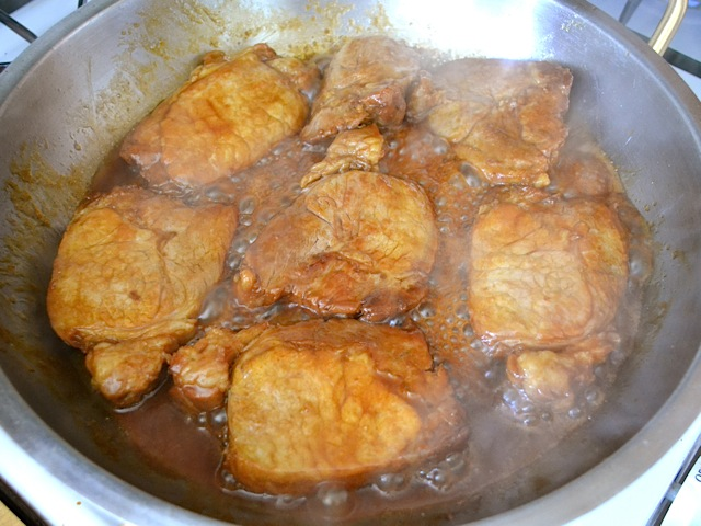 thickening sauce in pan of pork chops