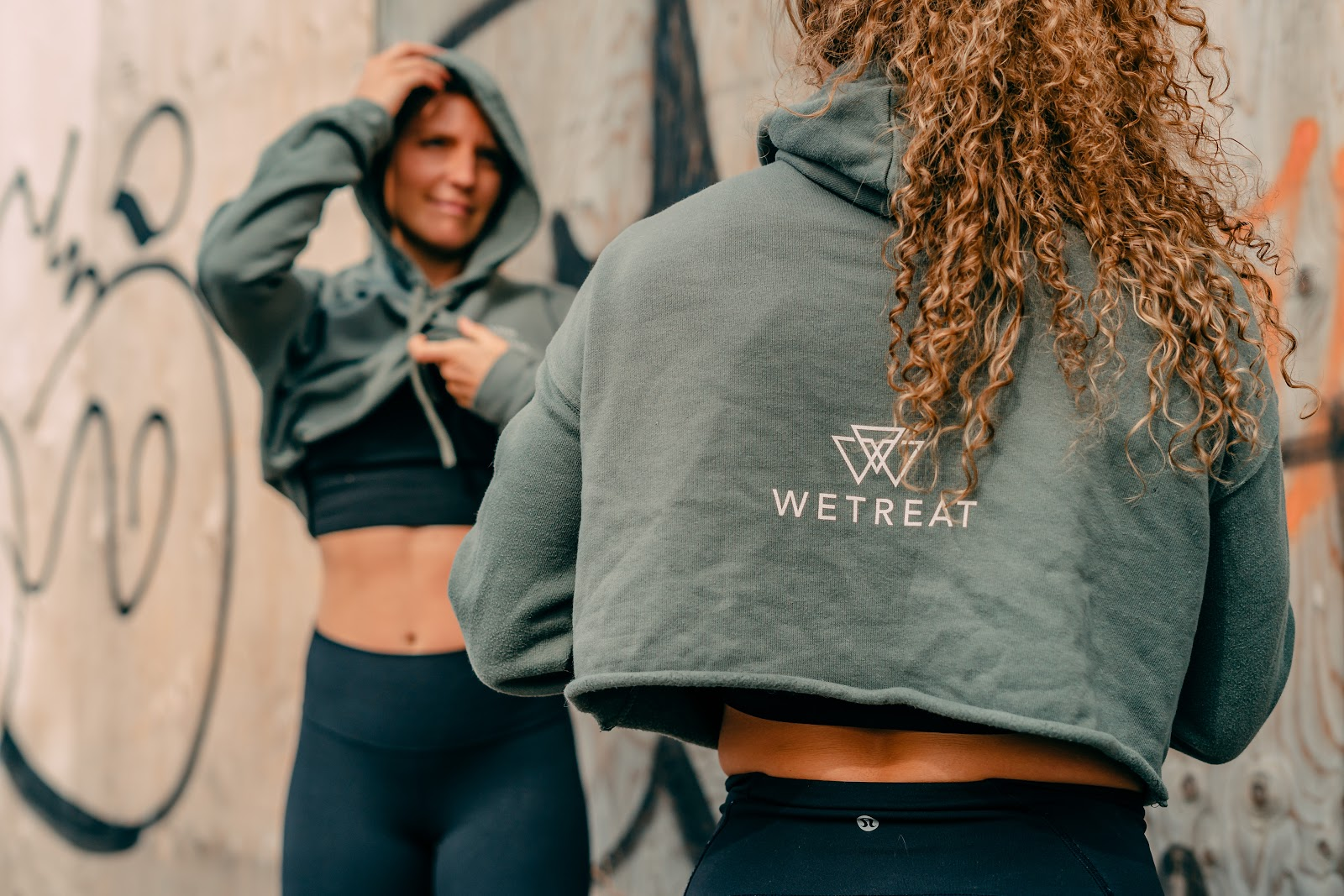 Two athletic women in hoodies wearing WETREAT custom screen print shirts by blankstyle.com